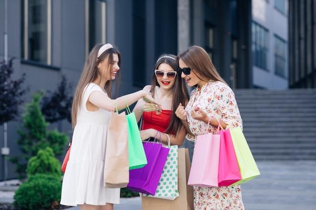 Группа молодых счастливых красивых женщин в повседневных платьях с цветами, топе и брюках с розовыми, желтыми, фиолетовыми и зелеными сумками для покупок, стоящих перед зданием и смотрящих на маникюр