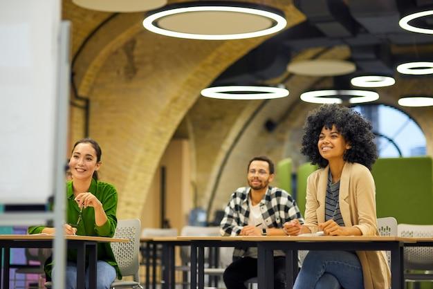 Группа молодых счастливых многорасовых людей, сидящих за столами в современном офисе и слушающих
