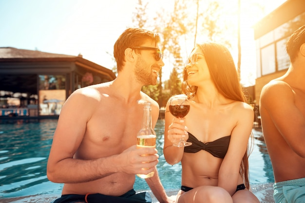 Группа молодых счастливых людей, сидящих у бассейна вместе