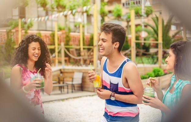 屋外の夏のパーティーで笑っている健康的な飲み物を持つ若い幸せな人々のグループ。柵越しの視点。
