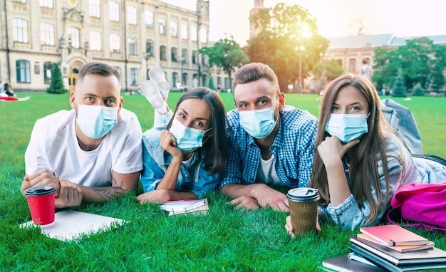 医療用マスクを身に着けた若い幸せな学生のグループは、大学で一緒に芝生に横たわって、カメラを見ています。屋外の芝生で休んでいる友達。