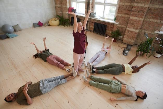 스포츠 훈련 헬스 클럽 동안 손을 들고 바닥에 운동하는 젊은 건강한 사람들의 그룹