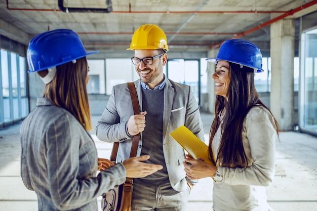 Группа молодых очень мотивирует привлекательных кавказских архитекторов в шлемах на головах, стоящих в здании в процессе строительства и беседующих во время паузы.