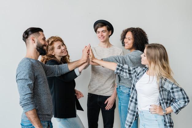 Группа молодых межкультурных друзей в повседневной одежде приветствует друг друга у белой стены