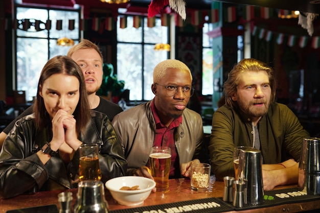 Группа молодых межкультурных друзей в повседневной одежде стоит у барной стойки с напитками и закусками во время просмотра футбольной трансляции в пабе
