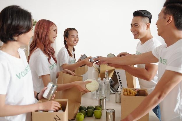 기부된 식료품을 분류하고 판지 상자에 음식을 넣는 즐거운 젊은 자원 봉사자 그룹