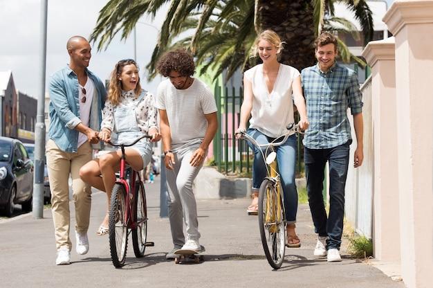 自転車とスケートボードを一緒に楽しむ若い男性と笑顔の女性のグループ