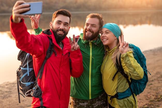 穏やかな湖の海岸で自分撮りをしながらvサインを示すバックパックを持つ若い男性と女性のグループ