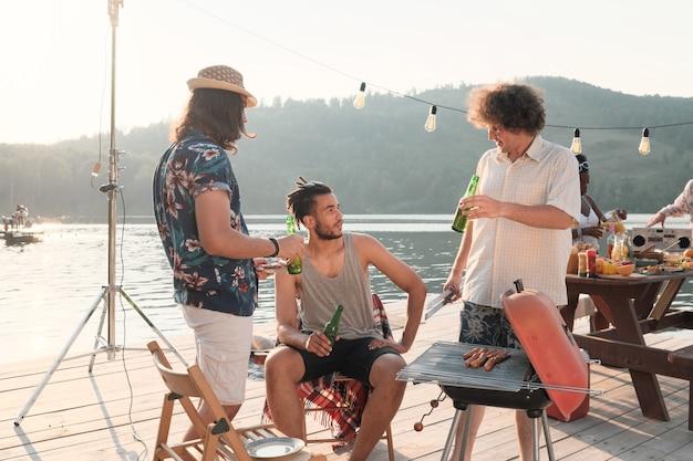 Группа молодых людей пьет пиво и разговаривает друг с другом во время вечеринки на пирсе