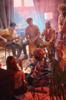 Группа молодых людей, играющих на музыкальных инструментах, выступает для своих друзей в студии