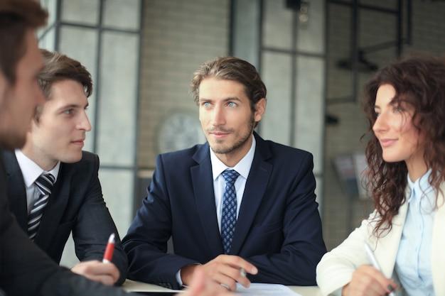 Группа молодых современных людей в формальной одежде, улыбаясь и что-то обсуждая, работая в современном офисе