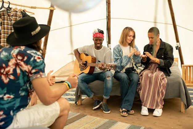 Группа молодых многоэтнических друзей сидит в палатке и слушает гитарную музыку в исполнении темнокожего парня