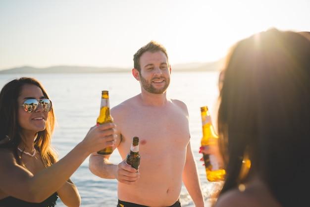 Группа молодых многонациональных друзей пляж лето