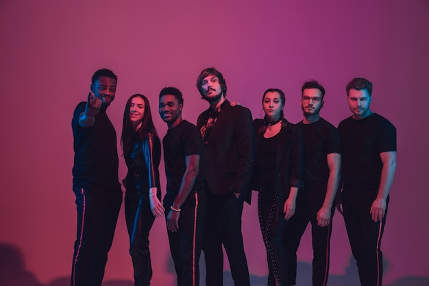 Группа молодых многонациональных музыкантов создала ансамбль, танцующий в неоновом свете на розовом фоне. понятие музыки, хобби, фестиваля, благополучия. радостный ведущий вечеринки, танцор, певец, гитарист, саксофонист.
