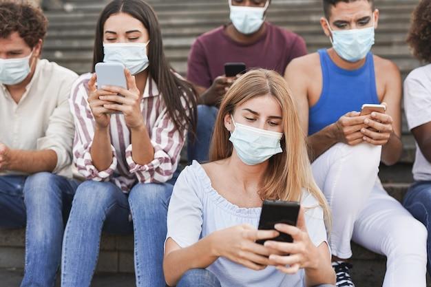 コロナウイルスの発生のためにサージカルフェイスマスクを着用しながら街の階段に座っている若い多民族の友人のグループ