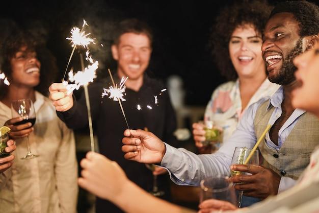 젊은 다인종 사람들의 그룹은 폭죽과 칵테일과 함께 새해 전날을 축하합니다