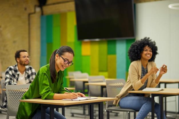Группа молодых многорасовых людей, сидящих за столами в современном офисе и слушающих