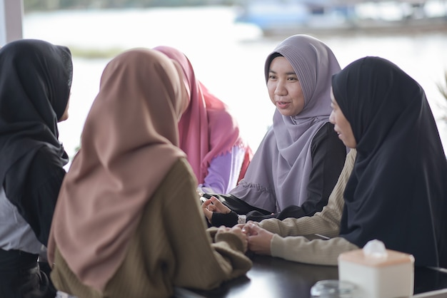 お互いに話しているカフェに座っている若いイスラム教徒のアジアのティーンエイジャーのグループ