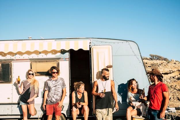 友情の中で一緒に夏の屋外レジャー活動の晴れた日を楽しんでいるヴィンテージキャラバンの外に立っている若者の代替千年紀の若い男性と女性のグループ