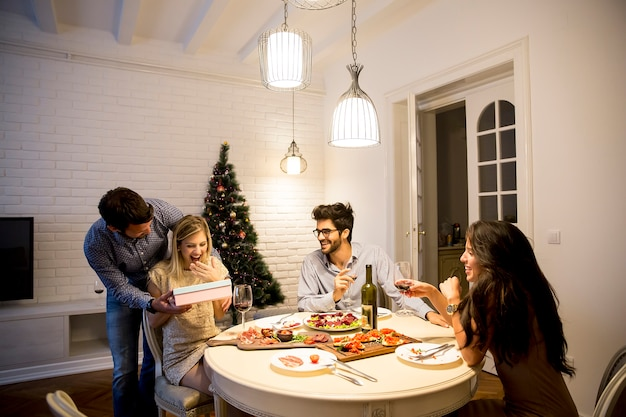 Группа молодых людей празднует рождество и открывает подарки в гостиной