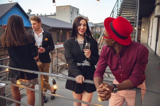Группа молодых людей празднует, выглядят счастливыми, устраивают корпоративную вечеринку в офисе или баре