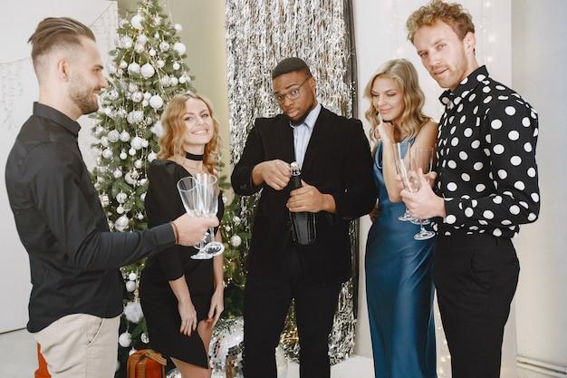 Группа молодых людей, празднующих новый год. друзья пьют шампанское.