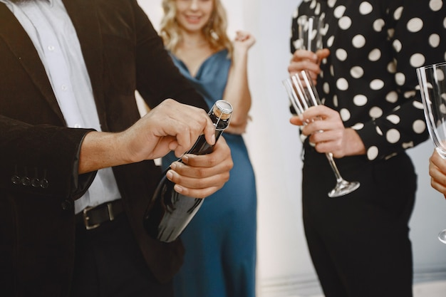 新年を祝う若者のグループ。友達はシャンパンを飲みます。