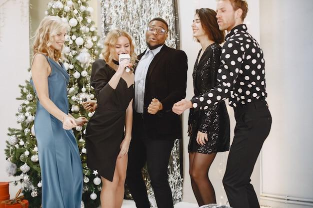 새 해를 축 하하는 젊은 사람들의 그룹입니다. 친구들은 샴페인을 마신다.