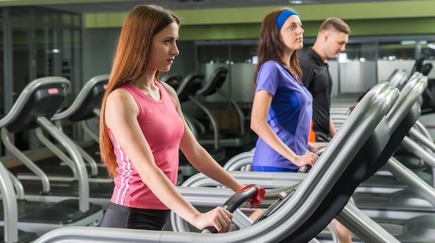 Группа молодых людей, усердно тренирующихся на беговой дорожке в фитнес-центре