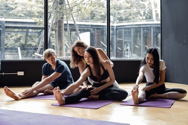 Группа молодых людей, занимающихся йогой на коврике для йоги, с тренером, постепенно обучающим в тренажерном зале. молодые женщины, мужчина и их учитель практикуют йогу в тренажерном зале. концепция упражнений с йогой.