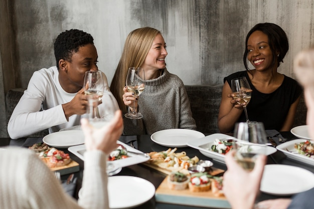 食べ物とワインを楽しむ若者のグループ