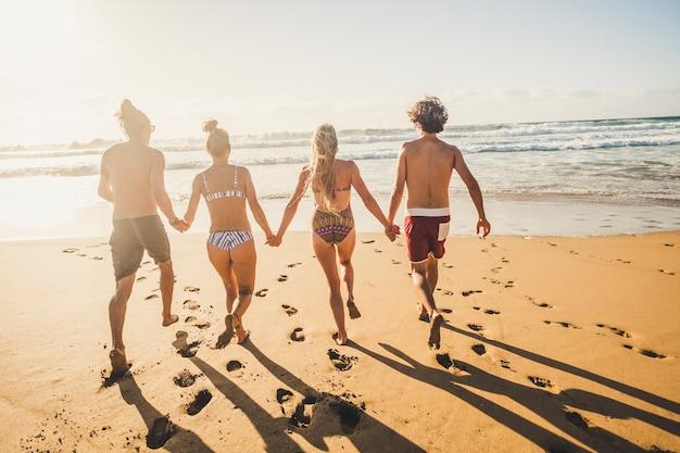 一緒に遊び心のあるアウトドアレジャー活動でビーチで水に向かって走る夏休みを楽しく楽しんでいる若者の友人のグループ-若い男性と女性