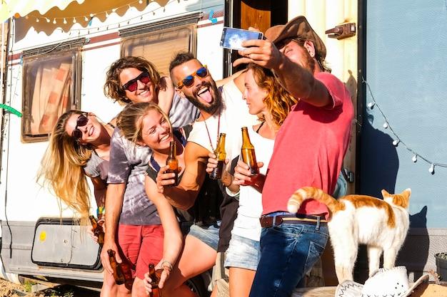若い友達のグループが、田舎の休暇のライフスタイルと古いキャラバンキャンピングカーで自撮り写真を撮る