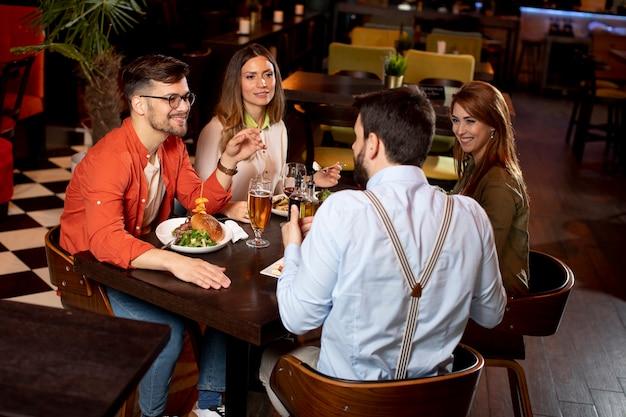 Группа молодых людей, обедающих в ресторане