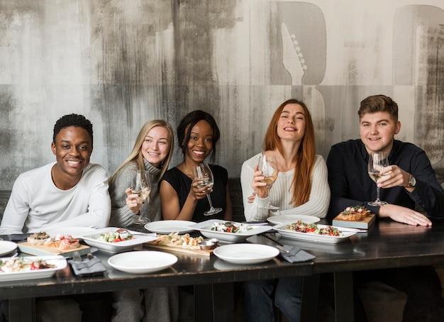 Группа молодых людей обедают вместе