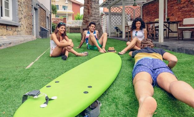 屋外で夏のサーフクラスを楽しんでいる若者のグループ。休日のレジャーの概念。
