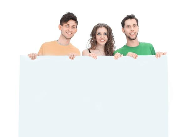 白い壁に隔離された大きな空白のポスターを保持している若者のグループ。