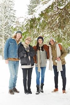 눈 덮인 겨울 숲에서 젊은 사람들의 그룹