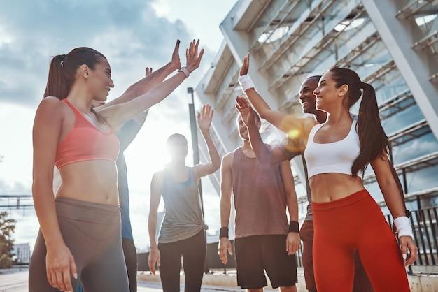 屋外で運動しながら互いに励まし合うスポーツウェアの若者のグループ