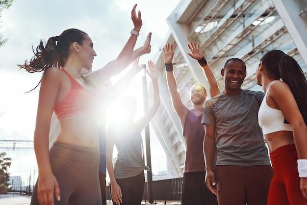 スポーツウェアを着た若者たちがハイタッチをし、屋外で運動しながら笑顔を見せているグループ