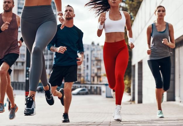 야외 보도에서 운동하는 동안 조깅 스포츠 의류에 젊은 사람들의 그룹