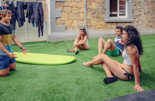 屋外の夏のクラスでサーフインストラクターを見ている若者のグループ。休日のレジャーの概念。