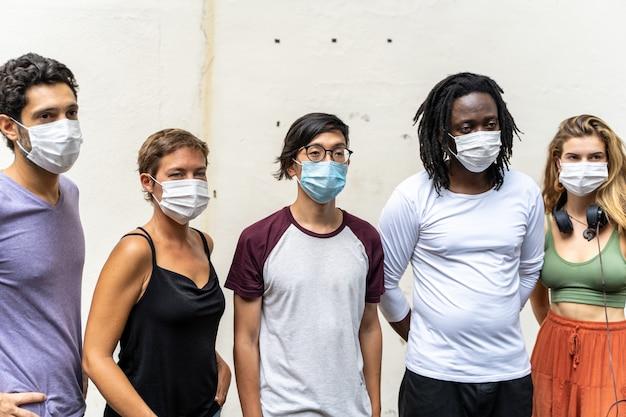 彼らの顔にマスクを持つさまざまな民族の若者のグループ
