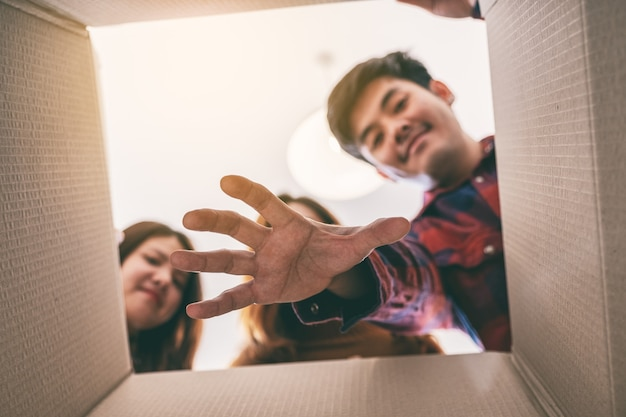 상자에서 선물을 열고 잡는 젊은 사람들의 그룹