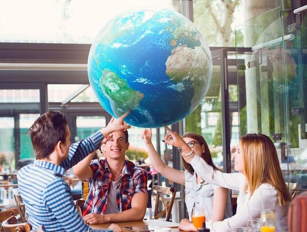 テーブルに座っている惑星地球を指している若者のグループ