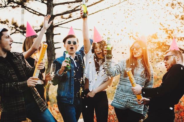 자연 속에서 크리스마스를 축하하는 동안 맥주 병을 제기하고 화려한 색종이로 파티 크래커를 폭발시키는 젊은 사람들의 그룹
