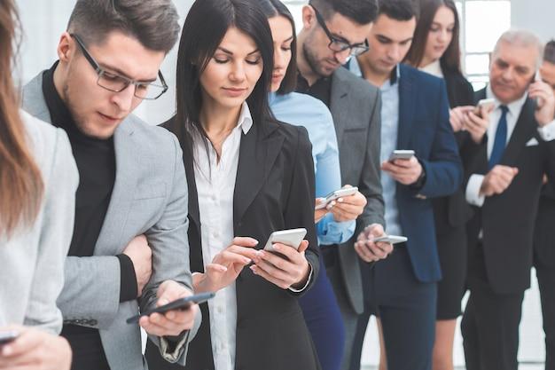 Группа молодых людей, читающих сообщения на своих смартфонах