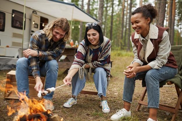 森のコピースペースで友達とキャンプを楽しみながらマシュマロを焼く若者たちのグループ