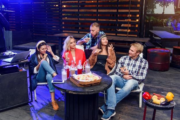 Группа молодых людей сидят и едят пиццу. друзья вечеринки и едят пиццу.
