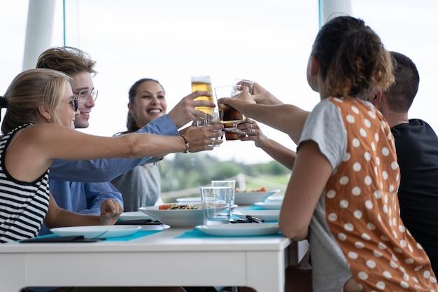 Группа молодых людей, сидящих за белым столом с пустыми тарелками тостов